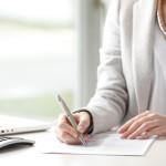 Frau am Schreibtisch füllt Praktikumsnachweis aus