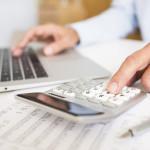 Rechnungsvorlage in Aktion - Mann mit Laptop und Taschenrechner