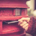Englischer Geschäftsbrief wird in roten Briefkasten geworfen