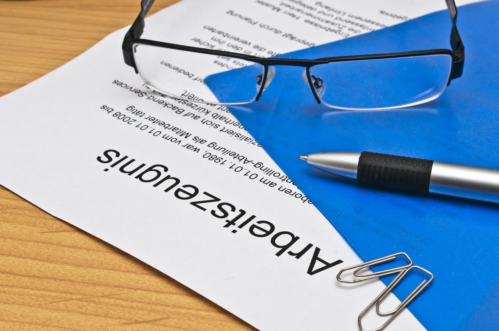 Brille und Kugelschreiber auf Arbeitszeugnis