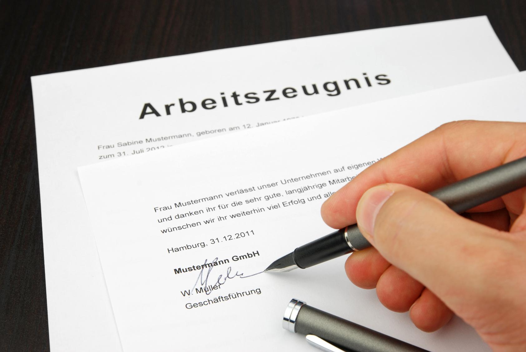 Arbeiszeugnis wird unterzeichnet (Hand sichtbar)