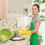 Frau mit Handschuhen spült in der Küche