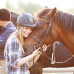 Junge Frau umarmt ihr Pferd