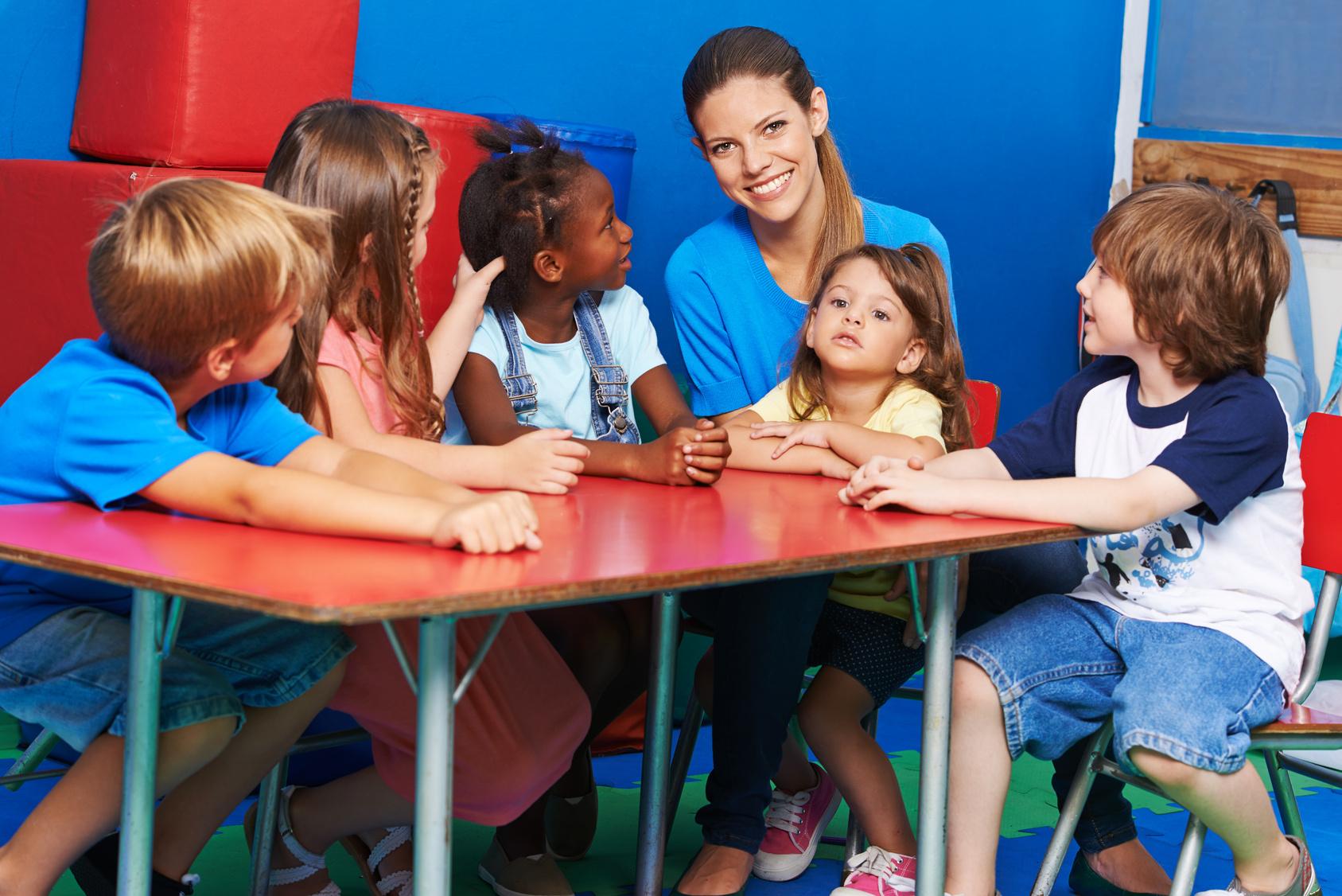 Gruppe Kinder sitzt mit Praktikantin im Kindergarten