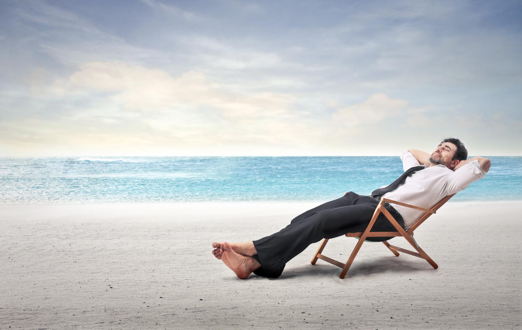 Mann im Anzug liegt im Strandstuhl